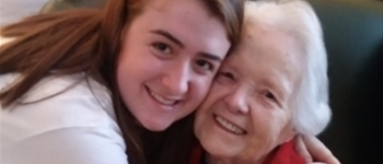Young female hugging elderly woman